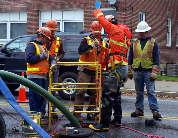 Workers from Clear Drains of Maine lower a camera down a manhole to see into a sewer pipe under Main Street in Norway on Wednesday.
